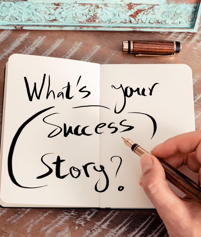 Retro effect and toned image of a woman hand writing a note with a fountain pen on a notebook. Handwritten text WHAT'S YOUR SUCCESS STORY ?, business success concept